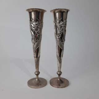 A pair of Chinese silver fluted vases decorated with dragons