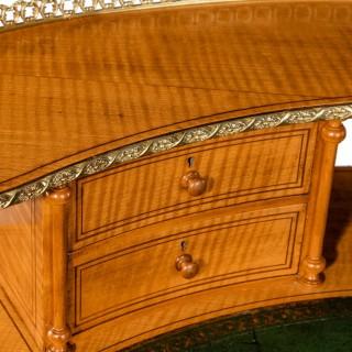 An unusual Victorian freestanding oval satinwood desk