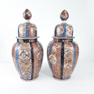 A pair of Japanese Imari jars and covers