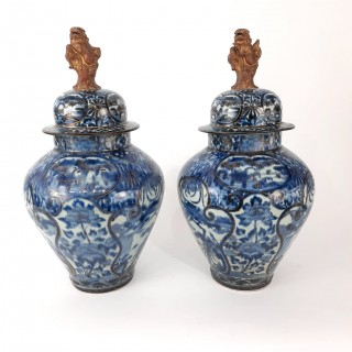 A pair of Japanese blue and white Imari vases and covers