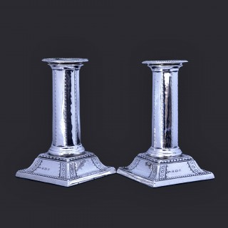 A pair of Liberty silver arts and crafts candlesticks by Bernard Cuzner