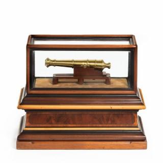 A miniature brass cannon in a presentation case