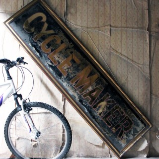 A Large Early 20thC Reverse Glass Painted Cycle Maker Advertising Sign c.1930-35