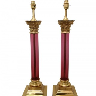 PAIR OF EARLY 20TH CENTURY CRANBERRY GLASS AND GILT BRONZE CORINTHIAN CAPITAL TABLE LAMPS