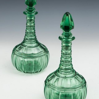 A PAIR OF ELABORATELY CUT GREEN VICTORIAN DECANTERS