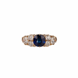 A good C19 th carved half hoop with a natural sapphire set between nice old mine cut diamonds