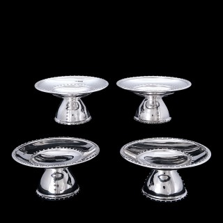 A set of four silver arts and crafts dishes with rivet design