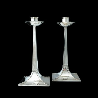 An early pair of classic James Dixon arts and crafts silver candlesticks
