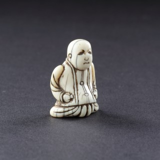 An Unusual Japanese Ivory Netsuke of a Dutch Merchant Kneeling in his Buttoned Coat and Baggy Trousers
