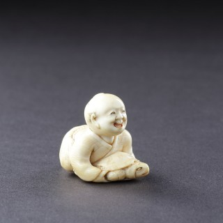 An Expressive Ivory Netsuke of a Young Japanese Fisherman Who has Caught a Ten Thousand Year Turtle