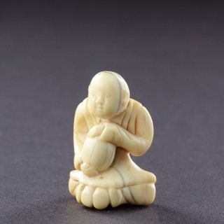 A Japanese Ivory Netsuke of a Man Seated Wearing a Mon Decorated Kimono Clasping with Both Hands his Treasured Saké Gourd