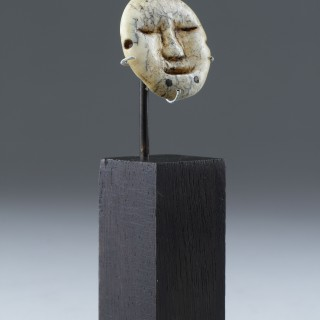 A Bering Strait Eskimo Inuit carved walrus ivory earring in the form of a human face