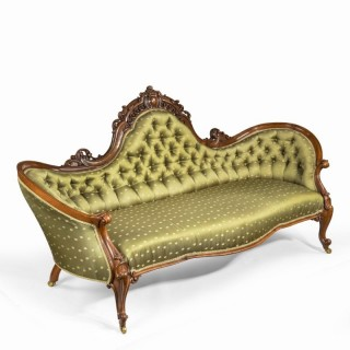 An elaborate Victorian shaped walnut sofa