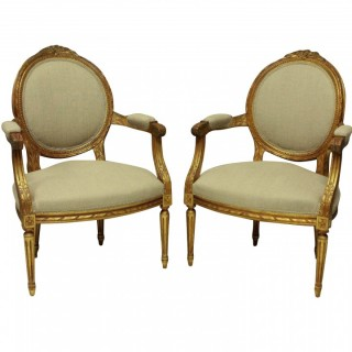 A PAIR OF LOUIS XVI STYLE GILT WOOD ARMCHAIRS