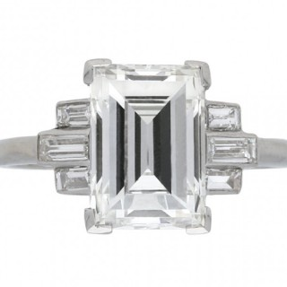 Art Deco flanked solitaire step cut diamond ring, circa 1925.