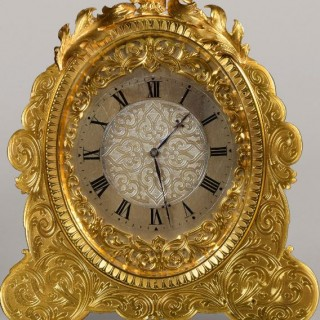 STRUT TIMEPIECE. A LATE VICTORIAN PERIOD GILT ENGRAVED OVAL STRUT TIMEPIECE IN THE MANNER OF THOMAS COLE.