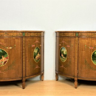 A  fine pair of mid 20th century satinwood three door demi-lune side cabinets embellished with hand painted cameo scenes and stylised floral decoration.